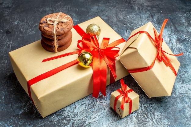 Vorderansicht weihnachtsgeschenke mit süßen keksen an hell-dunklen feiertagen fotogeschenk weihnachtsfarbe neujahr