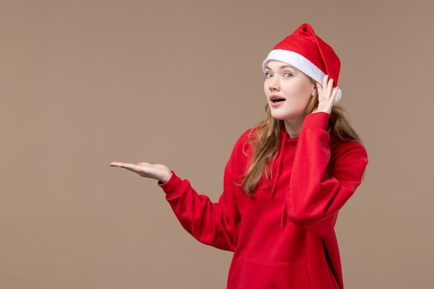Vorderansicht-weihnachtsmädchen, das auf braunem hintergrund neujahrs-weihnachtsfeiertag hört