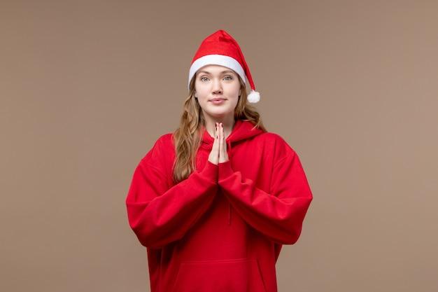 Vorderansicht-weihnachtsmädchen, das auf dem braunen hintergrundfeiertagsmodell weihnachten betet