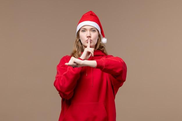 Vorderansicht-weihnachtsmädchen, das auf den weihnachtsemotionen des braunen hintergrundfeiertags aufwirft