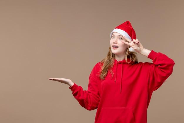 Vorderansicht-weihnachtsmädchen, das auf neujahrsweihnachten des braunen hintergrundfeiertags aufwirft