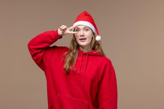 Vorderansicht-weihnachtsmädchen, das auf weihnachtsemotion des braunen hintergrundfeiertags aufwirft