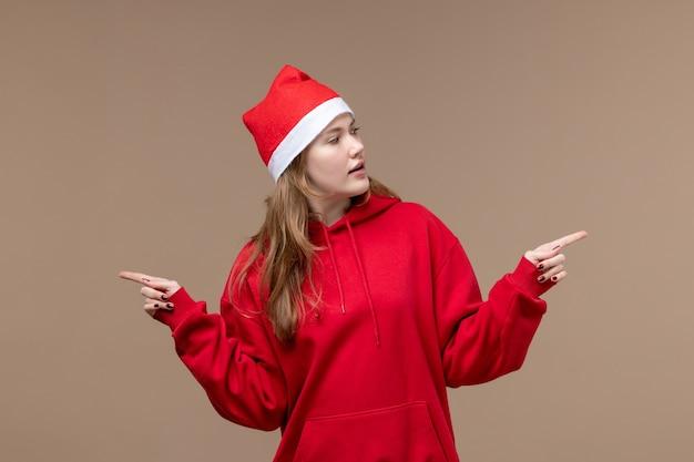 Vorderansicht-weihnachtsmädchen, das auf weihnachtsfeiertagsemotion der braunen hintergrundfrau aufwirft