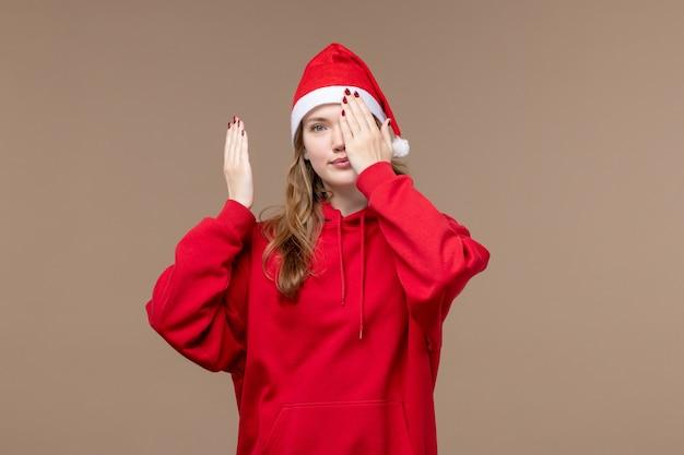 Vorderansicht-weihnachtsmädchen, das ihr gesicht auf braunem hintergrundmodellfeiertagsweihnachten bedeckt