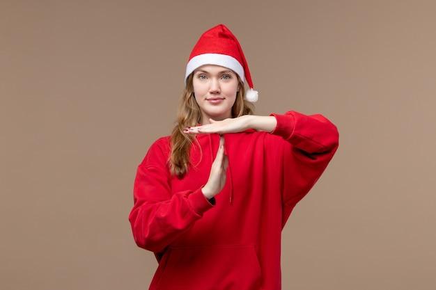 Vorderansicht-weihnachtsmädchen, das mit lächeln auf der weihnachtsemotion des braunen hintergrundfeiertags aufwirft