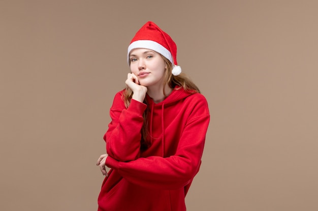 Vorderansicht-weihnachtsmädchen, das mit rotem umhang auf braunem hintergrundmodellfeiertagsweihnachten aufwirft