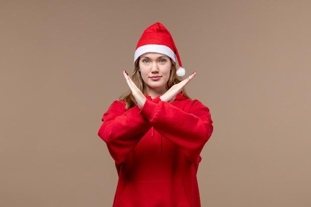 Vorderansicht-weihnachtsmädchen, das verbotszeichen auf braunem hintergrundmodellfeiertagsweihnachten zeigt