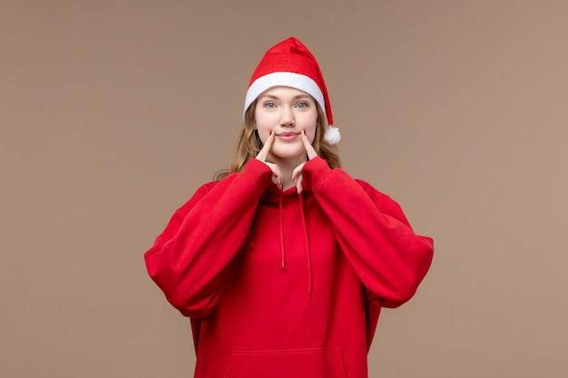 Vorderansicht-weihnachtsmädchen, das versucht, auf braunem hintergrundmodellfeiertagsweihnachten zu lächeln