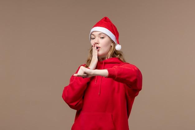 Vorderansicht-weihnachtsmädchen, das zeit auf der weihnachtsemotion des braunen hintergrundfeiertags prüft