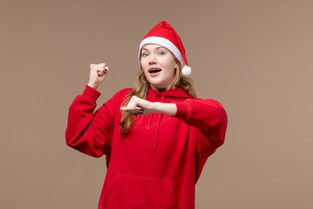 Vorderansicht-weihnachtsmädchen, das zeit auf weihnachtsfeindlichkeiten des braunen hintergrundfeiertags prüft