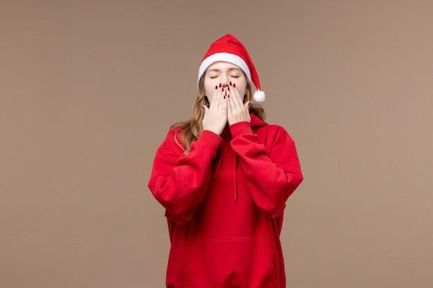 Vorderansicht weihnachtsmädchen gähnt auf braunem hintergrund frau feiertage weihnachten