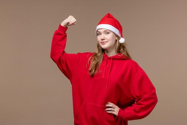 Vorderansicht weihnachtsmädchen lächelnd und biegend auf braunem hintergrundfeiertagsweihnachtsgefühl