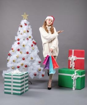 Vorderansicht-weihnachtsmädchen mit bunten einkaufstüten, die die richtige richtung zeigen