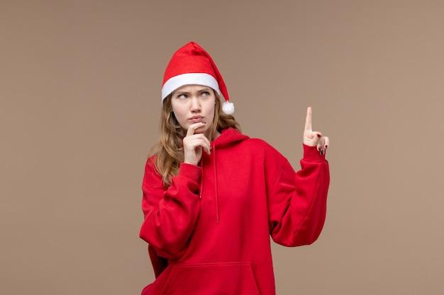 Vorderansicht-weihnachtsmädchen mit denkendem ausdruck auf weihnachtsfeiertagsweihnachten des braunen hintergrunds