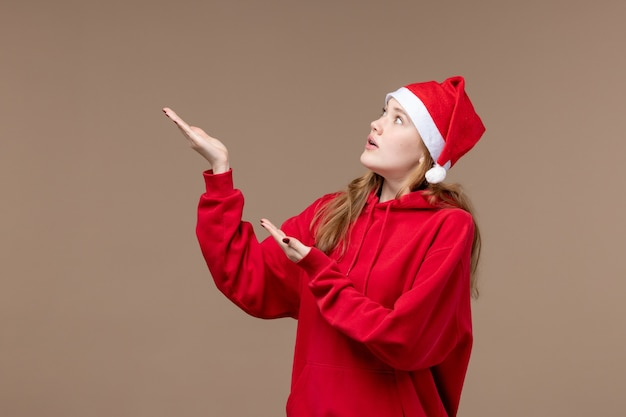 Vorderansicht-weihnachtsmädchen mit nervösem gesicht auf braunem raum