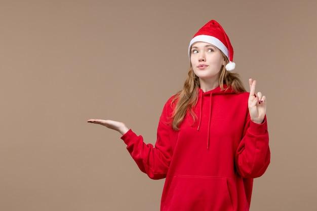 Vorderansicht weihnachtsmädchen mit rotem umhang auf braunem boden feiertage neujahr weihnachten