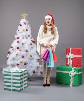 Vorderansicht-weihnachtsmädchen mit weihnachtsmütze, die bunte einkaufstaschen nahe weihnachtsbaum hält