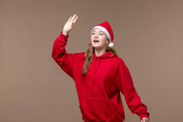 Vorderansicht-weihnachtsmädchen winken und grüßen auf braunem hintergrundfeiertagsmodell weihnachten