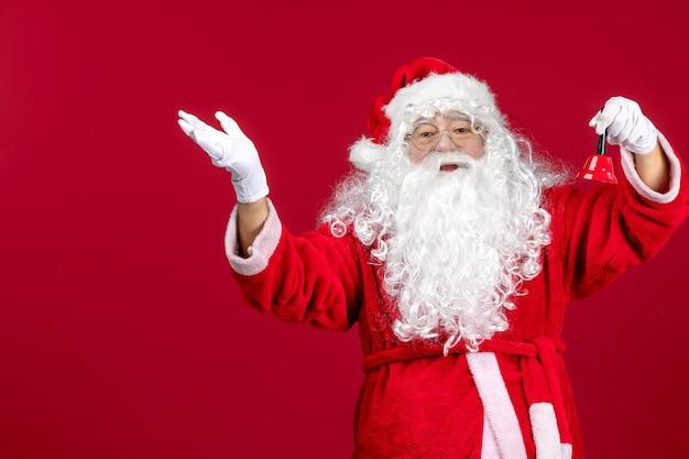 Vorderansicht weihnachtsmann, der kleine glocke auf rotem geschenkgefühl weihnachtsfeiertag neues jahr hält
