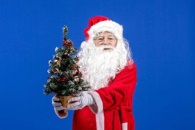Vorderansicht weihnachtsmann, der kleinen neujahrsbaum auf blauer schneefarbe hält