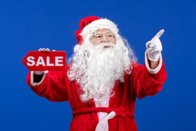 Vorderansicht weihnachtsmann, der rote verkaufsschrift auf blauem bodenfarbe schneeurlaub neues jahr weihnachten hält