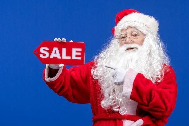 Vorderansicht weihnachtsmann, der rote verkaufsschrift auf der blauen farbe schneeferien neues jahr weihnachten hält