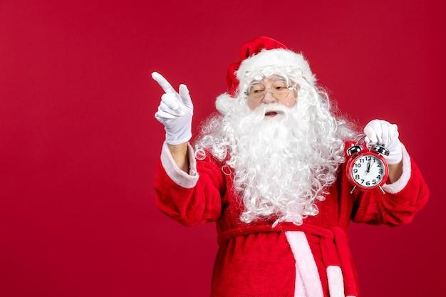Vorderansicht weihnachtsmann, der uhr an einem roten weihnachtsemotionsurlaub hält