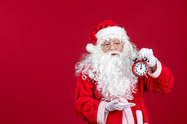Vorderansicht weihnachtsmann, der uhr auf rotem weihnachtsneujahremotionsurlaub hält