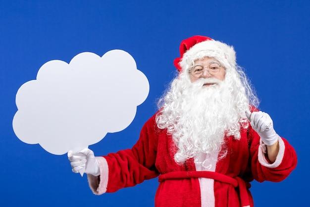 Vorderansicht weihnachtsmann hält großes wolkenförmiges schild auf blauem schneefarbe weihnachtsfeiertag