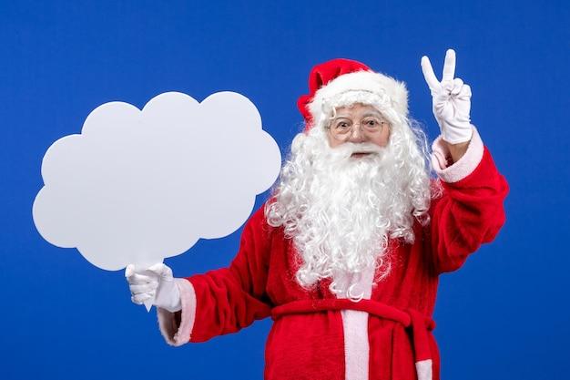 Vorderansicht weihnachtsmann hält großes wolkenförmiges schild auf blauem schreibtisch schneeweihnachtsfarbe