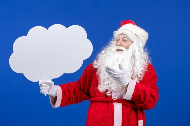 Vorderansicht weihnachtsmann hält großes wolkenförmiges zeichen auf der blauen schneefarbe weihnachten