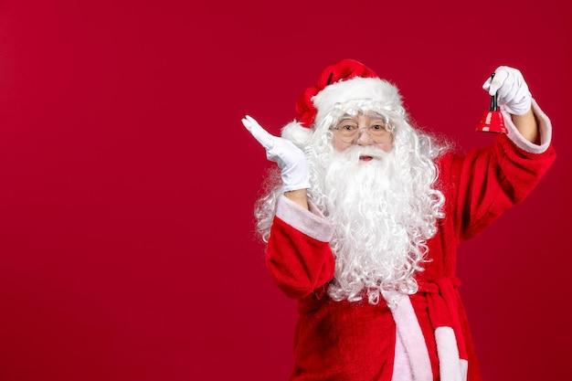 Vorderansicht weihnachtsmann hält kleine glocke auf dem roten geschenk emotion weihnachten neujahr urlaub