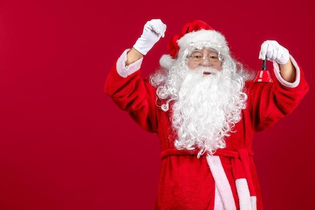 Vorderansicht weihnachtsmann hält kleine glocke auf dem roten weihnachtsgeschenk emotion urlaub