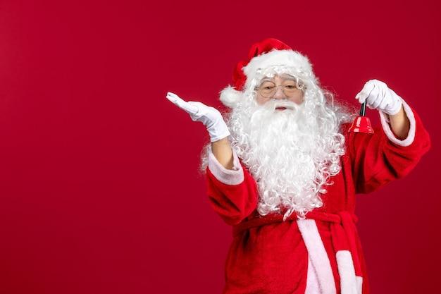 Vorderansicht weihnachtsmann hält kleine glocke auf einem roten schreibtisch geschenk emotion weihnachten urlaub neujahr