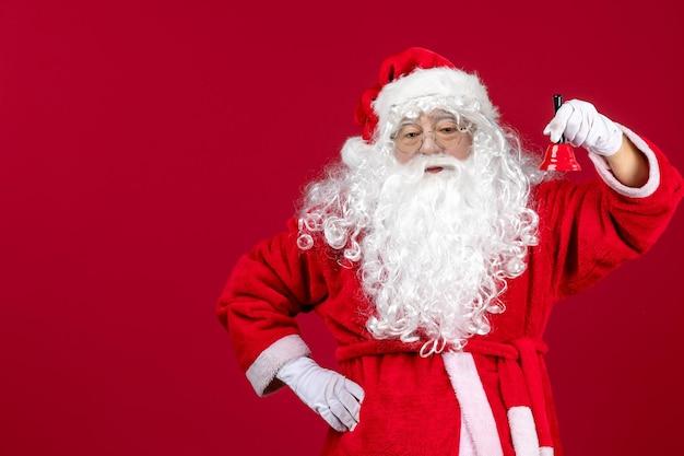 Vorderansicht weihnachtsmann hält kleine glocke auf rotem boden weihnachten neujahr geschenk emotion urlaub