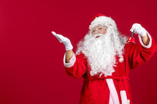 Vorderansicht weihnachtsmann hält kleine glocke auf rotem geschenk emotion weihnachtsfeiertag