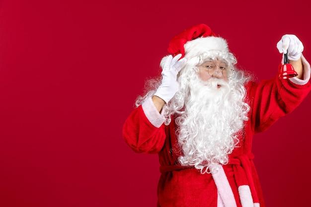 Vorderansicht weihnachtsmann hält kleine glocke auf rotem geschenk weihnachtsfeiertag neujahr emotion