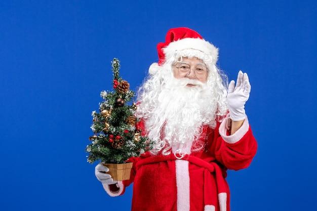 Vorderansicht weihnachtsmann hält kleinen neujahrsbaum auf blauem schnee neues jahr weihnachten