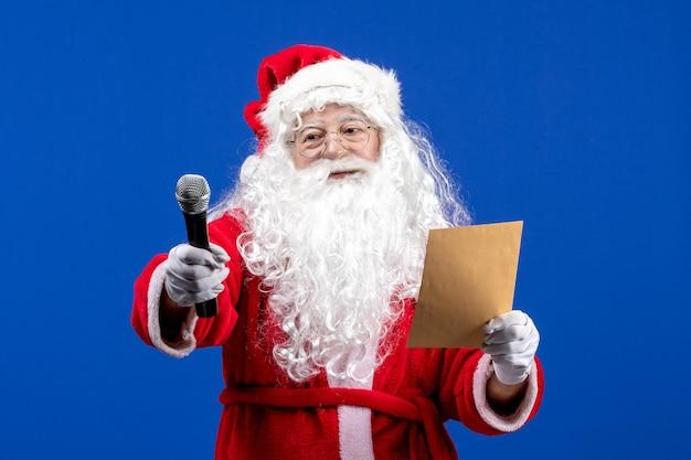 Vorderansicht weihnachtsmann hält mic und liest brief auf blauem neujahr farbe ferien weihnachten schnee