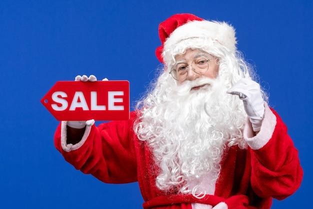 Vorderansicht weihnachtsmann hält rote verkaufsschrift auf blauem schreibtisch farbe schnee urlaub neues jahr weihnachten