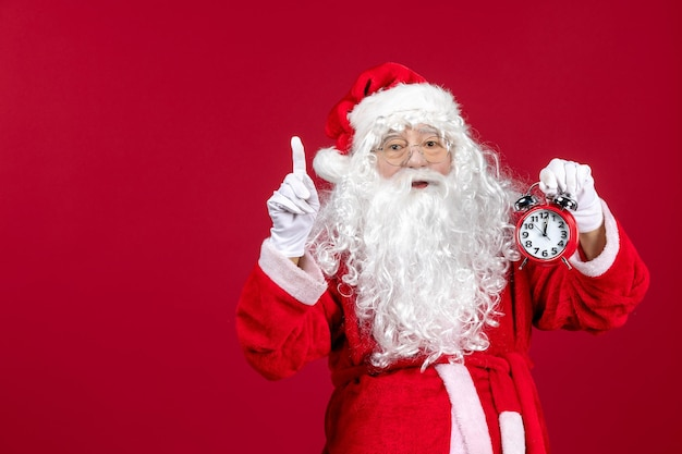 Vorderansicht weihnachtsmann hält uhr auf rotem schreibtisch weihnachten neujahr emotion