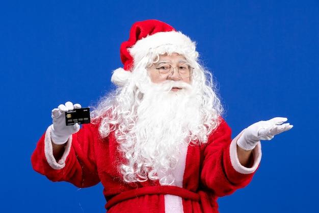 Vorderansicht weihnachtsmann im roten anzug mit schwarzer bankkarte auf blauem weihnachtsfarbenurlaub