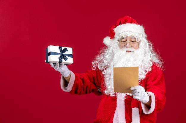 Vorderansicht weihnachtsmann liest brief vom kind und hält geschenk an roten emotionsgeschenk weihnachtsferien