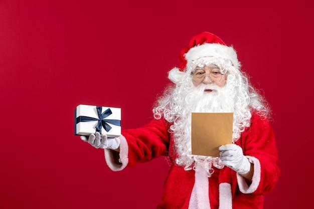 Vorderansicht weihnachtsmann liest brief vom kind und hält geschenk auf dem roten emotionsgeschenk weihnachtsfeiertag
