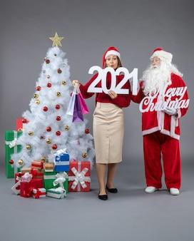 Vorderansicht-weihnachtsmann mit der jungen frau, die und frohe weihnachten auf dem grauen hintergrund hält