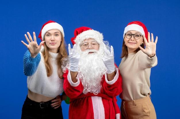 Vorderansicht weihnachtsmann mit frauen, die auf dem blauen farbgefühl des neuen jahres weihnachtsschnee posieren