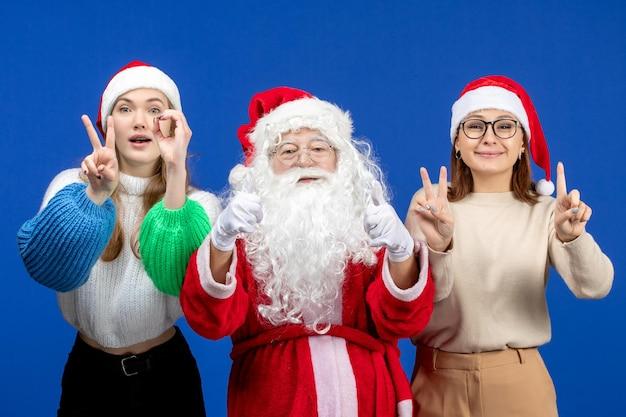 Vorderansicht weihnachtsmann mit frauen, die nur auf blauem schnee des neuen jahres weihnachtsgefühl stehen