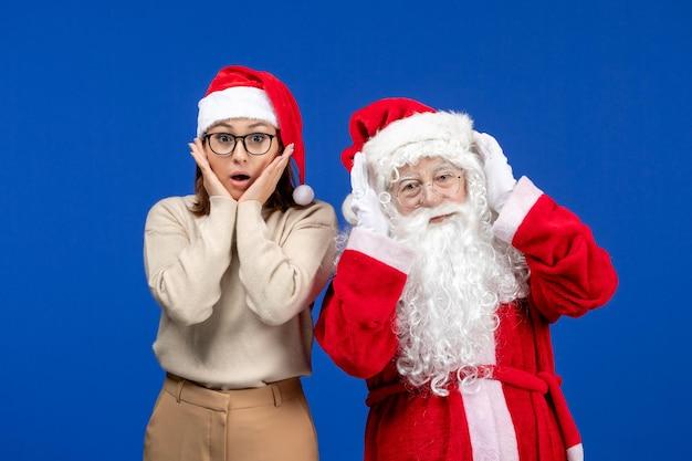 Vorderansicht weihnachtsmann mit hübscher frau, die auf dem blauen schnee des neuen jahres steht