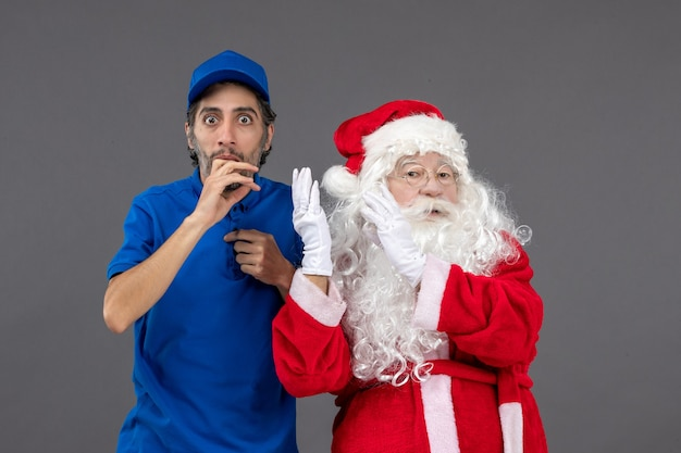 Vorderansicht weihnachtsmann mit jungem männlichem kurier auf grauem hintergrund