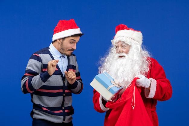 Vorderansicht weihnachtsmann mit jungem mann, der geschenkbeutel hält